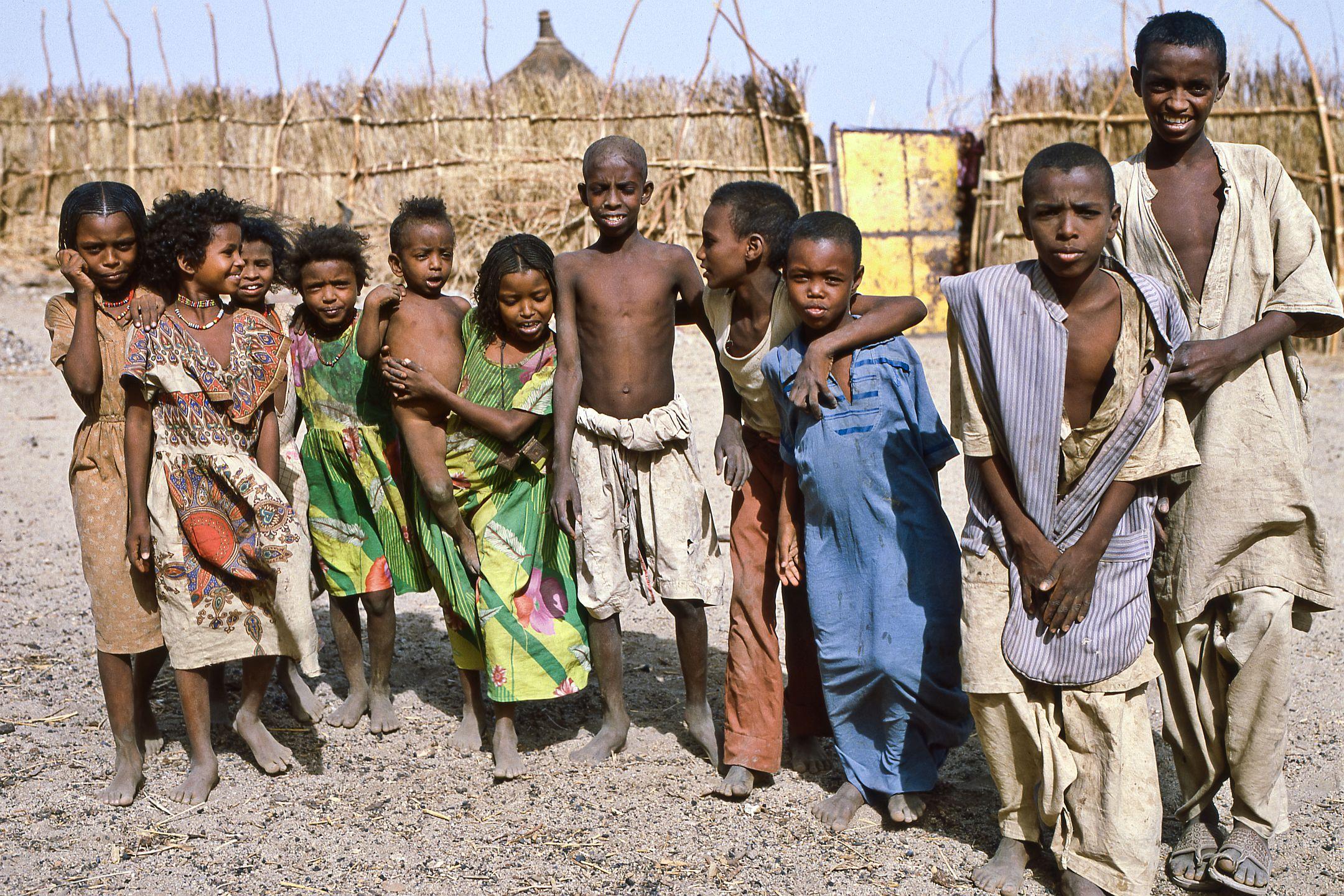 In Kassala, Sudan kann es um diese Jahreszeit über 40°C werden. Da wenig Regen fällt, zeigt sich die Natur am Siedlungsrand der Stadt wenig bewachsen. Die Kinder zeigen sich neugierig und als Gruppe mutig genug um für ein Foto zu posieren. Auch hier gehören die kleineren Kinder dazu. Ein schönes Bild einer Kindergemeinschaft! Erkennbar ist auch, dass die beiden Ältesten bereits nicht mehr Teil dieser Gruppe sind.