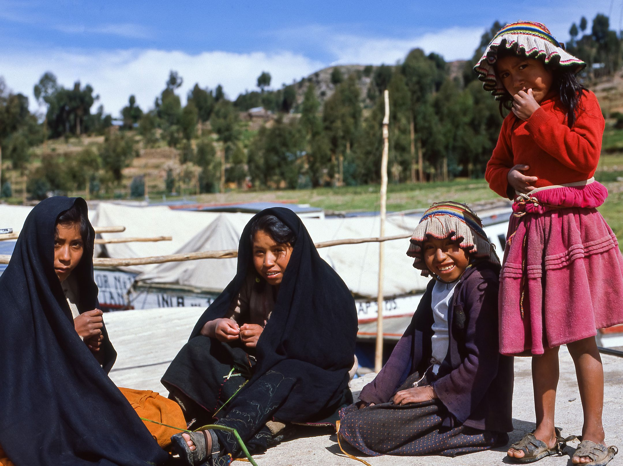 Titicacasee in Peru. Auf der Insel Amantani sind wir Gäste bei einer Indiofamilie. Bei einem Rundgang treffen wir an der Schiffsanlegestelle auf diese vier Mädchen. Zwei tragen die hier typische Form von Hut. Der flache Oberteil ist Zentrum eines reihum gewellten Stoff-Vorhangs.